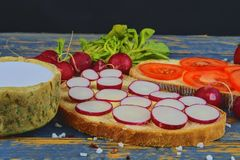 Spread butter on bread with sliced tomatoes and radishes. Fresh snack on natural wooden background.  Stock Images