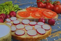 Spread butter on bread with sliced tomatoes and radishes. Fresh snack on natural wooden background.  Stock Photo