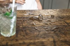 Spread water with ice cubes on vintage wooden table. Spread water on a vintage table made of light wood with scuffs and scratches next to transparent relief royalty free stock images