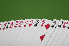 Spreaded cards. A couple of poker cards spread out on a green surface Stock Photo