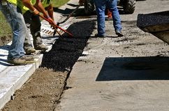 Spreading asphalt on curb repair project Royalty Free Stock Image