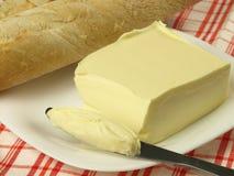Spreading butter. On fresh tasty baguette Stock Photos