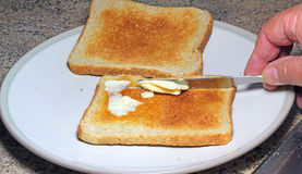Spreading butter on toast. Royalty Free Stock Photography