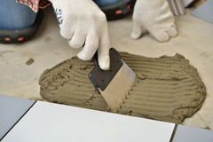 Spreading cement during tiled floor installation Royalty Free Stock Photography