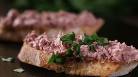 Spreading chopped parsley over liverwurst sandwich on a dark slate stock video footage