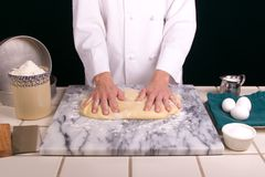 Spreading Dough. Close up on a uniformed female Baker's hands spreading bread dough into a a rectangle for making dinner rolls on a cold marble board Stock Images