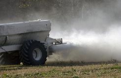 Spreading fertiliser. Spreading a cloud of fertiliser over a wheat stubble field Stock Photography