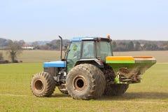 Spreading fertilizer. A tractor spreading fertilizer in springtime under a blue sky Royalty Free Stock Photos