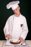 Spreading Filling. Passive posed smiling female Pastry Chef spreading white buttercream filling atop a chocolate devil's food cake layer with a cake spatula Royalty Free Stock Images