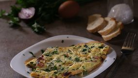 Spreading fresh chopped parsley over omelet made from eggs, bacon, cheese stock footage