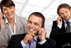 Spreading the good news. Three happy business people talking on their cellular phones stock image