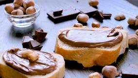 Spreading hazelnut chocolate cream on bread closeup stock footage