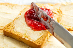 Spreading jam on bread. Toasted bread butter and jam on plate stock images
