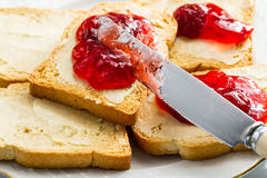 Spreading jam on bread. Toasted bread butter and jam on plate stock photo