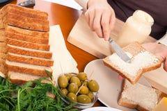 Spreading mayonnaise on sandwich stock photos