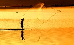 Spreading The Net. A fisherman spread his net to catch fish in a lake stock photo