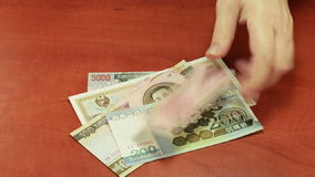 Spreading North Korean banknotes stock footage