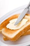 Spreading peanut butter on toast Stock Photography