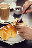 Spreading Preserves on a Croissant Roll in a Cafe Royalty Free Stock Image