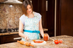 Spreading sauce on a pizza. Young woman in an apron adding some tomato sauce to her homemade pizza Stock Images