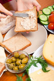Spreading tuna spread on sandwich Royalty Free Stock Images