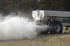 Spreading white fertiliser. Spreading a cloud of white fertiliser over a wheat stubble field Stock Image