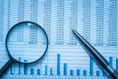 Spreadsheet bank accounts accounting finance forensics with magnifying glass and pen. Concept for financial fraud investigation.