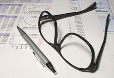 Spreadsheets and glasses. Male businessman work glasses and pen with spreadsheets for sales Royalty Free Stock Image