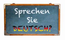 """""""Sprechen西埃德意志?在德语的†,您是否讲德语?写在一个宽蓝色老脏的葡萄酒木黑板 免版税库存照片"""