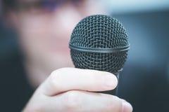Sprechen im Mikrofon: Junger Mann mit undeutlichem Gesicht nimmt in das Mikrofon stockfotografie