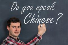 Sprechen Sie Chinesisch? Mann mit Kreideschreiben auf Tafel lizenzfreies stockbild