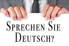 Sprechen sie deutsch? do you speak german? written in german. A man wearing a suit holding a signboard with the sentence sprechen sie deutsch? do you speak Stock Photo