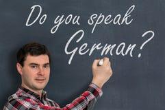 Sprechen Sie Deutsch? Mann mit Kreideschreiben auf Tafel Stockfotos