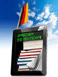 Sprechen Sie Deutsch? - Tablet Computer. Black tablet computer with pages and phrase Sprechen Sie Deutsch? on display, stack of books and German flag on a blue Stock Photography