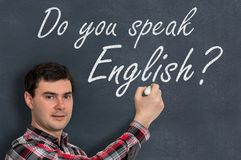 Sprechen Sie Englisch? Mann mit Kreideschreiben auf Tafel Lizenzfreies Stockfoto