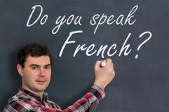Sprechen Sie französisch? Mann mit Kreideschreiben auf Tafel Stockfoto