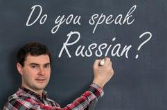 Sprechen Sie Russisch? Mann mit Kreideschreiben auf Tafel Stockfotografie