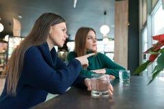 Sprechende junge Frauen, Mädchen, die im Café lächelnd und sprechend, trinkendes Trinkwasser im Glas, das Fenster heraus schauend stockfotografie