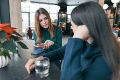 Sprechende junge Frauen, Mädchen, die im Wintercafé lächelnd und sprechend sitzen, trinkendes Trinkwasser im Glas und mit Handy,  stockbilder