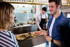 Sprechende Paare beim Essen des Weins durch Zähler Stockfoto