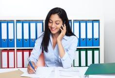 Sprechende türkische Geschäftsfrau mit Telefon im Büro lizenzfreies stockfoto