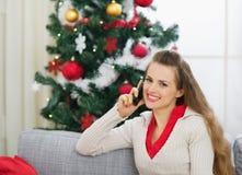 Sprechender Handy der Frau nahe Weihnachtsbaum Stockbild