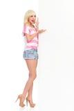 Sprechendes blondes Mädchen, das auf weiße große Fahne zeigt Stockfotografie