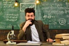 Sprecher bei der Hochschulsitzung im Konferenzklassenzimmer, alte Bücher auf einem runden Holztisch, Mann, der im Laptop schaut Lizenzfreie Stockfotos