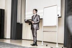Sprecher hält eine Darstellung eines neuen Finanzprojektes und steht vor einem leeren Werbung Brett in modernem Stockbild