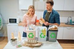 Spreco che ordina a casa Giovani coppie sorridenti che mettono plastica, carta, l'altro spreco nei bio- recipienti dell'immondizi immagini stock
