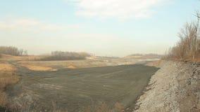 Spreco da estrazione del carbone nera, da materiali di riporto e dagli scarichi, ustione lenta del terreno incolto della cenere video d archivio