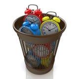 Spreco del concetto di tempo: sveglie nel bidone della spazzatura Fotografie Stock