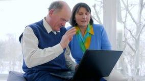 Spreekt de gepensioneerde videomededeling, oude mensen in skype thuis gebruikend laptop stock footage