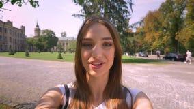 Spreekt de jonge vrouw van Nice in videochat in park in dag, die camera, communicatie concept houden stock video